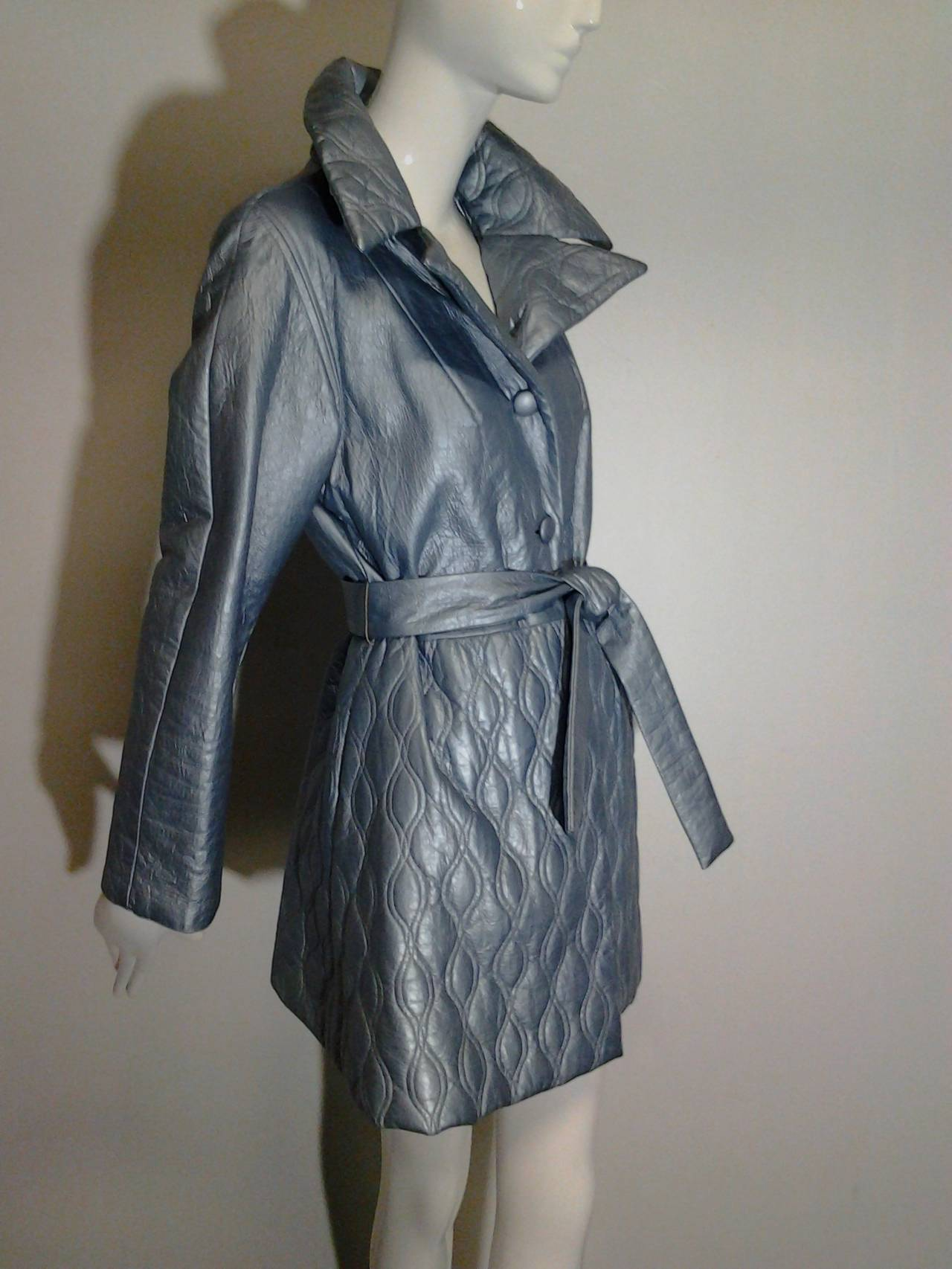 A 1960s Lilli Ann quilted pearlized pale blue vinyl car coat with button closures and self belt. Large peaked lapel collar