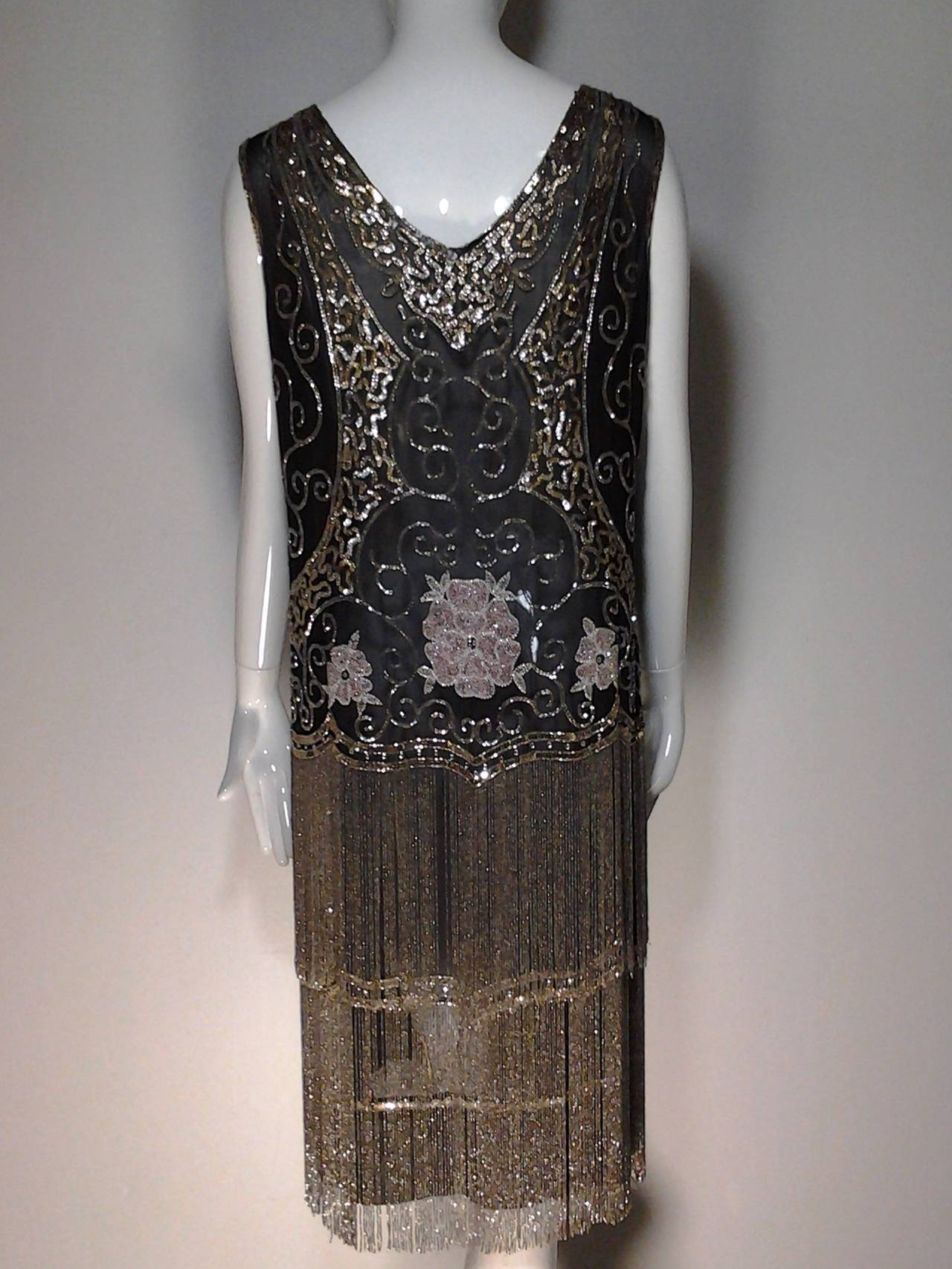 """1920s French Art Deco sheer silk crepe fringed """"flapper"""" dress:   Black fabric with sequin and beaded """"Arabesque"""" design.  Dropped waist skirt is heavily embellished with 2 tiers of silver beaded fringe measuring 9"""" each.   Flowers beaded in"""