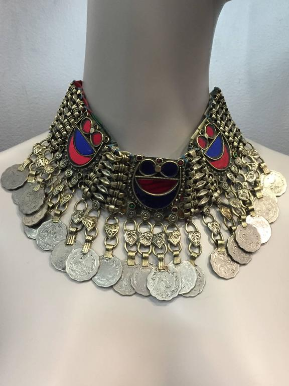 Ethnic coin bib necklace with tinted mirror tile inlay.  Closure is chain and hook.  Back is covered in back for smooth comfort.  Size is variable.
