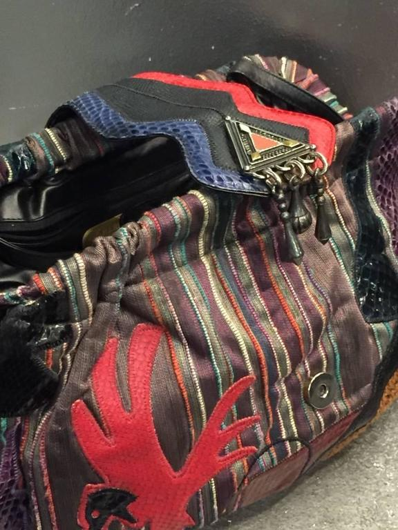 1980s Sharif multicolored and striped brocade handbag with snakeskin appliqués of birds and geometric shapes in various colors. Metal beaded clasp. Zippered pocket inside and optional black leather shoulder strap.