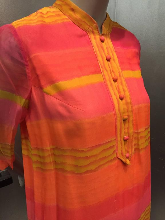 A wonderfully vibrant 1960s striped silk chiffon tunic style dress with button placket at front.  Fully lined in body, sheer in sleeves. In shades of orange, gold and fuchsia.
