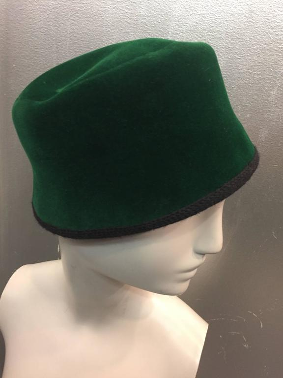 This1960s Christian Dior Evergreen Velvet Felt Fez has a chic black knit back bow.  The inside circumference measures 22 inches and is trimmed in black wool knit.  The crown measures 4 inches tall.  Made in France.