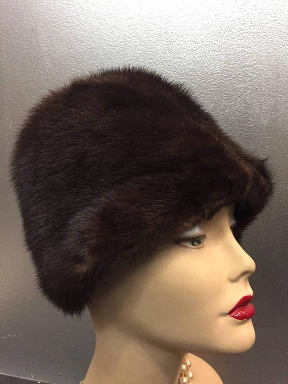 A warm and beautiful 1960s Saks Fifth Avenue natural mink cloche-style hat with rolled brim and pon pon. Completely lined.