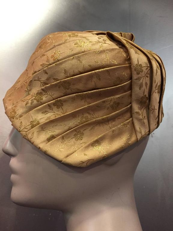 1950s Tatiana gold silk lamé brocade pleated asymmetrical cocktail hat with wired brim and grosgrain band.  Size medium.