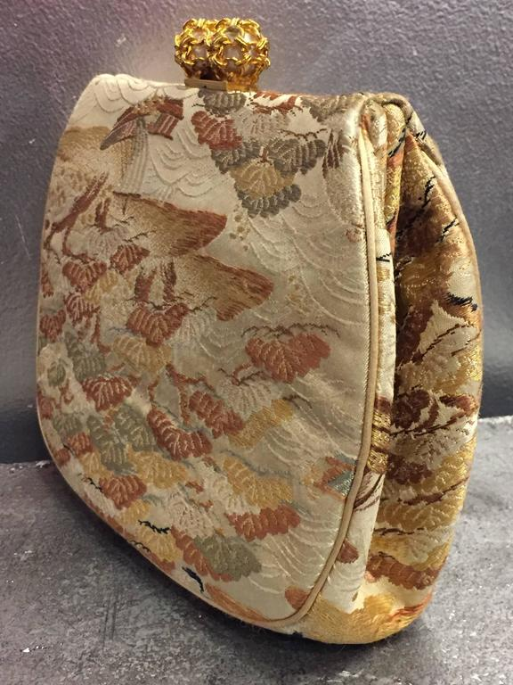 A beautiful 1950s Koret Asian silk fabric brocade clutch evening bag with faux gold and pearl clasp. Original change purse included.