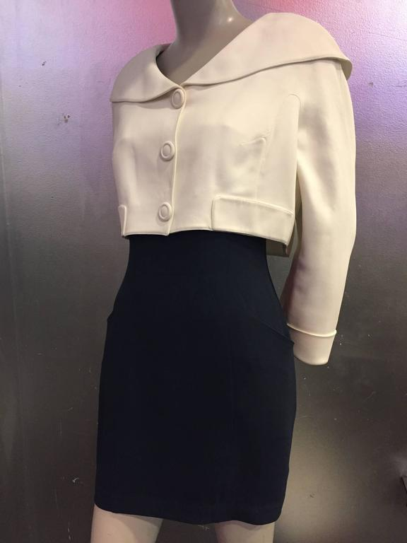 "A wonderful resort ""sailor-styled"" 1980s Thierry Mugler 2-piece dress and jacket ensemble:  Dress is in navy crepe, cut above the knee with wide straps and a cream band around the bust.  Cream jacket is cropped with a large rounded sailor"