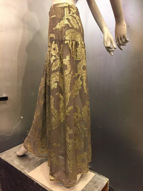 Late 1970s Saint Laurent taupe silk chiffon and gold metallic lamé paisley patterned maxi skirt with dropped waist panel and gold lamé piped hemline. Zippered back. Unlined.