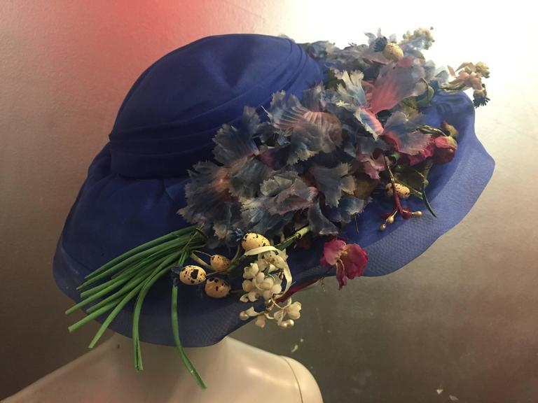 A lovely period hat with a very vintage feel. Featuring an unusual color of blue with various silk wildflowers in pastel colors.   The crown fits about a size medium.