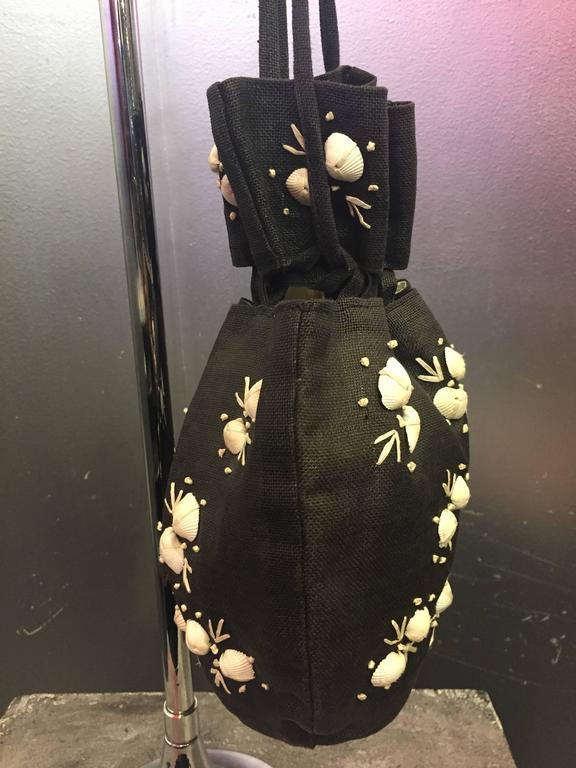 A wonderful drawstring style black straw pouch bag made of finely woven black straw. The exterior is adorned with real seashells and embroidery. Perfect for summer and resort attire.