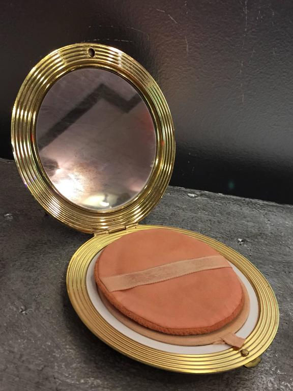 A striking art deco style compact with slightly domed lid. The original powder screen and puff are in excellent condition, but can be removed. Interior mirror is large and functional. Measures 5 inches by 5 inches.