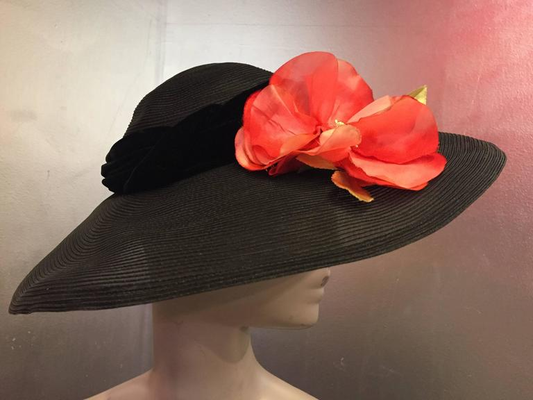 This beautiful 1950's Noreen Black sheer cartwheel had has a wonderful wide brim. The crown molds softly over the head and is accented by a braided velvet band with a fetching poppy in shocking red. Perfect for warm weather or any day at the races,