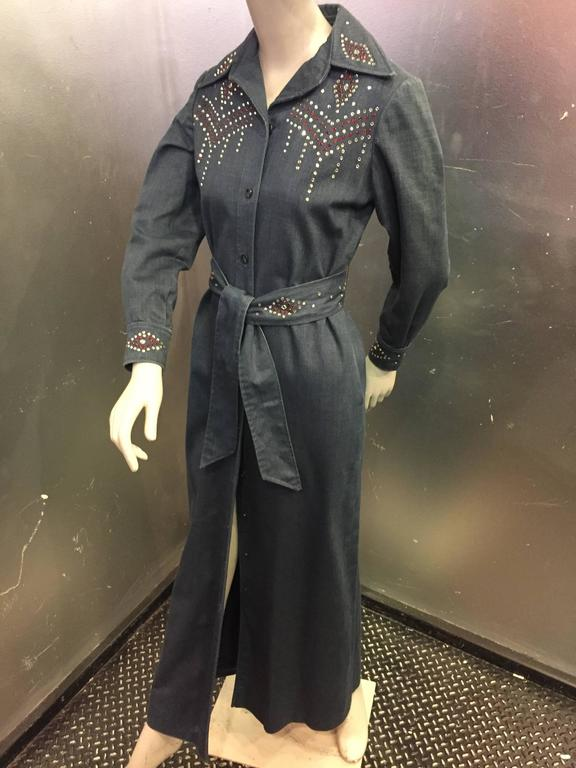 A fabulous Western rock star style denim maxi coat with red and white rhinestone studs. Studded at the neckline, bodice, back, belt and wristbands with classic Western wear patterns. Unlined, with side slit pockets. This is a true vintage