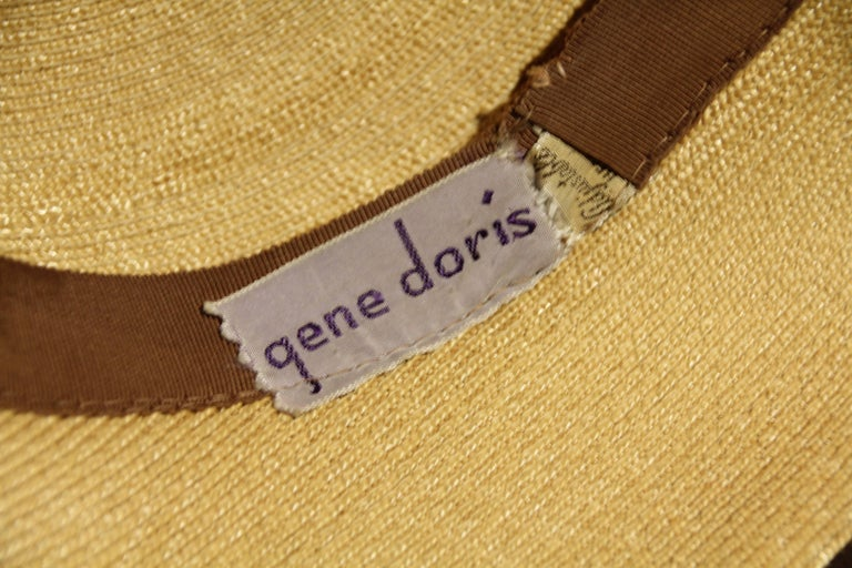 A charming 1940s Gene Doris sculpted brim natural straw hat with a narrow brown ribbon hat band and inner grosgrain band.