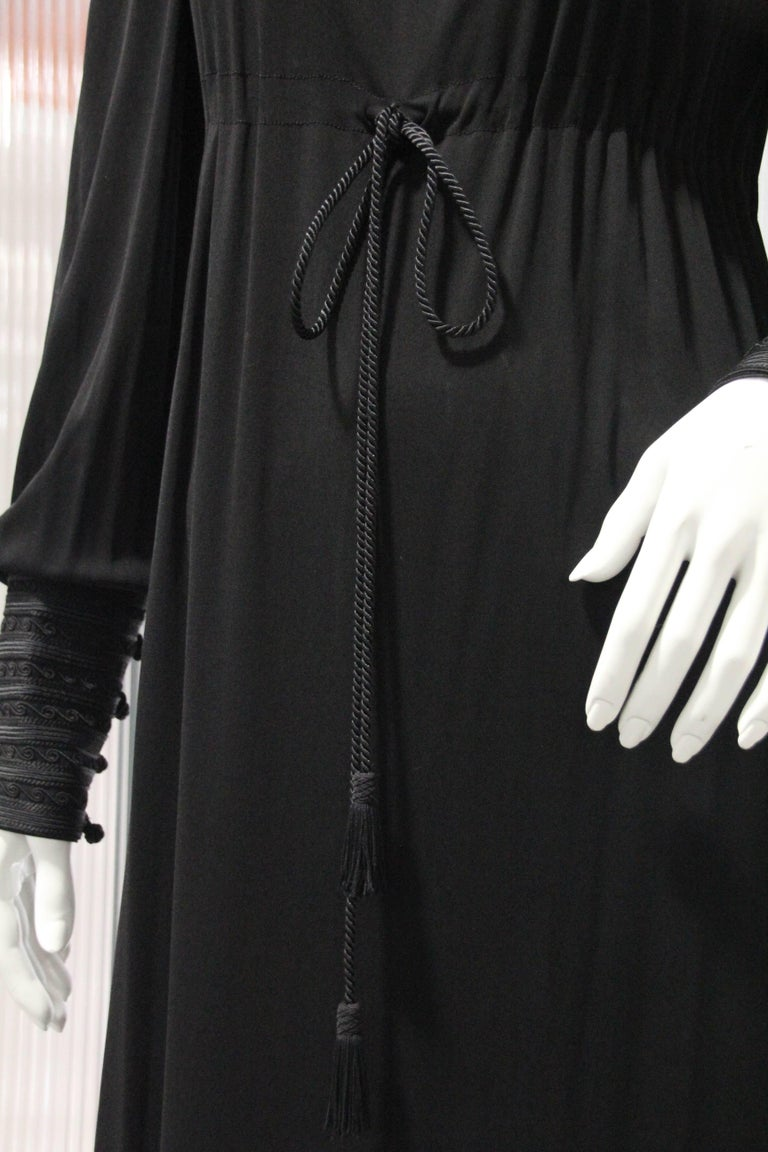 A beautiful 1970s Yves Saint Laurent black matte rayon jersey maxi dress with Moroccan-inspired style and braid trim at neckline. Draw string cord empire waist. Wide button and loop braid trimmed cuffs. Supremely comfortable, this piece has no