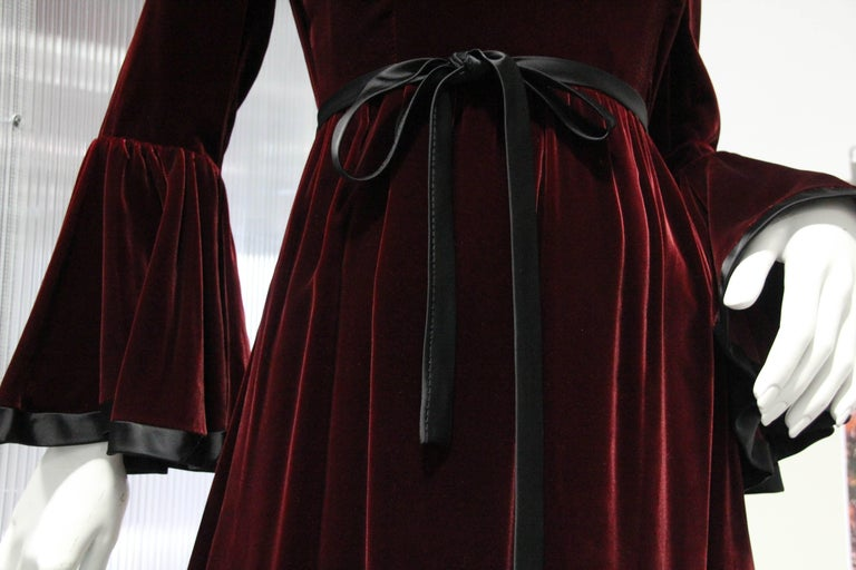 An exquisite late 1960s Ferdinando Sarmi Renaissance-Revival, burgundy velvet gown with flared cuffs and hem. Satin trim at cuffs and a thin satin tie waistband. zippered back.  Wonderful holiday attire!