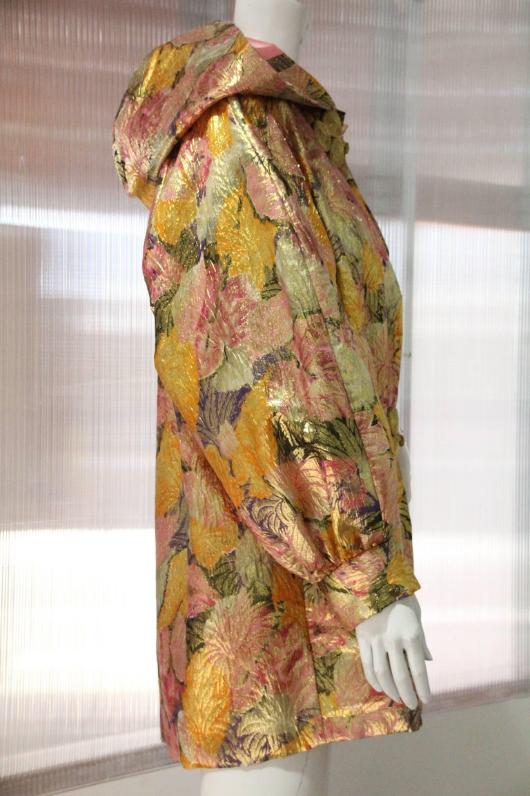 1980s Fernando Sanchez gold brocade bed jacket with pink silk satin lined hood and throughout body.  Full cut style with gold frog closure at neckline.  Side slit pocket, banded cuff and full puff sleeves. Fits a US size 10.