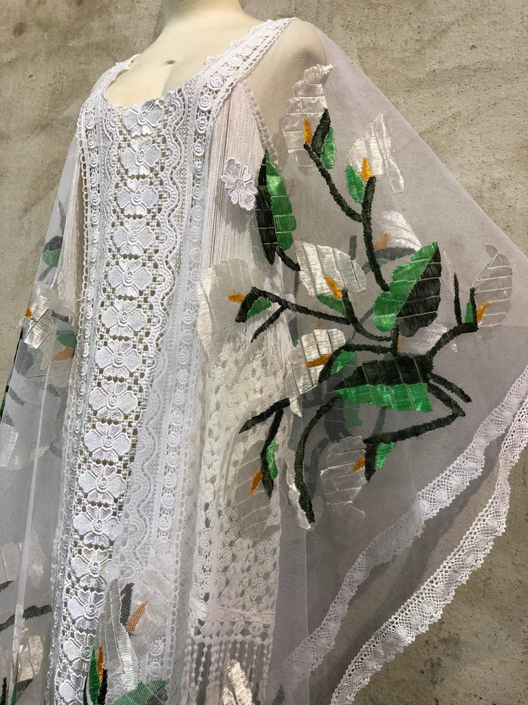 This stiff white mesh net Kaftan is silk embroidered with shades of green and white and yellow thread. Floral motif silk embroidery on each side panel create an etherial feel which is joined together with white machine-made lace at center front and
