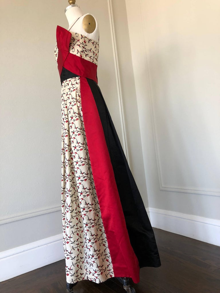 An elegant 1950s evening gown by Oleg Cassini features cream silk embroidered floral motif silk taffeta fabric with a red silk sash at the bodice and black silk satin backside.  This genius and spontaneous design make this gown modern and stylish in