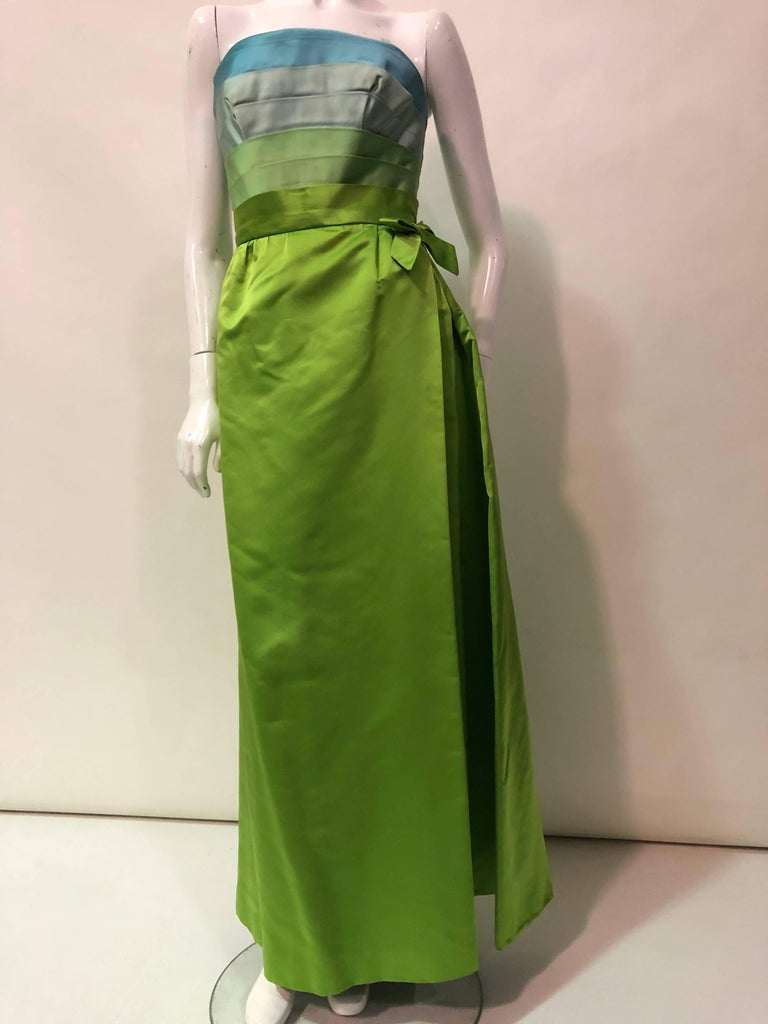 1950s Philip Hulitar silk satin column silhouette gown with aqua, turquoise and chartreuse pleated, strapless bodice.  Bodice is boned and structured.  Zipper at back.  Skirt has the appearance of a wrap-style with pleating and a bow at left side.
