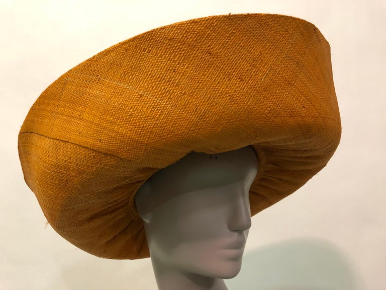 This dramatic orange woven straw hat is most likley from the 1980s  Large turned up brim adds drama to this Summer sunhat . Vintage fruit corsage at the back of hat adds a twist of whimsy . Fits up to a size large.