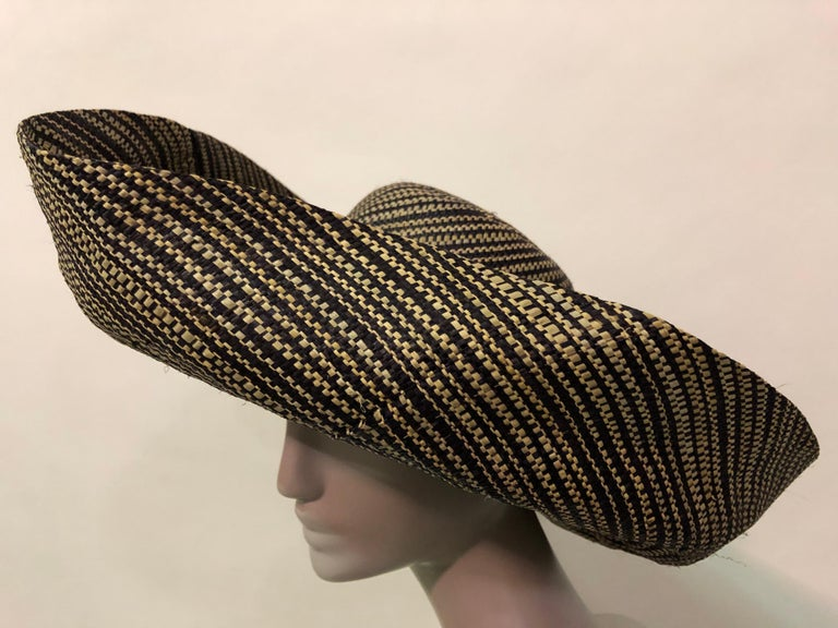 This dramatic 2 tone woven straw hat is most likely from the 1980s Large turned up brim adds drama to this Summer sunhat. Vintage fruit corsage at the back of hat adds a twist of whimsy. Fits up to a size large.