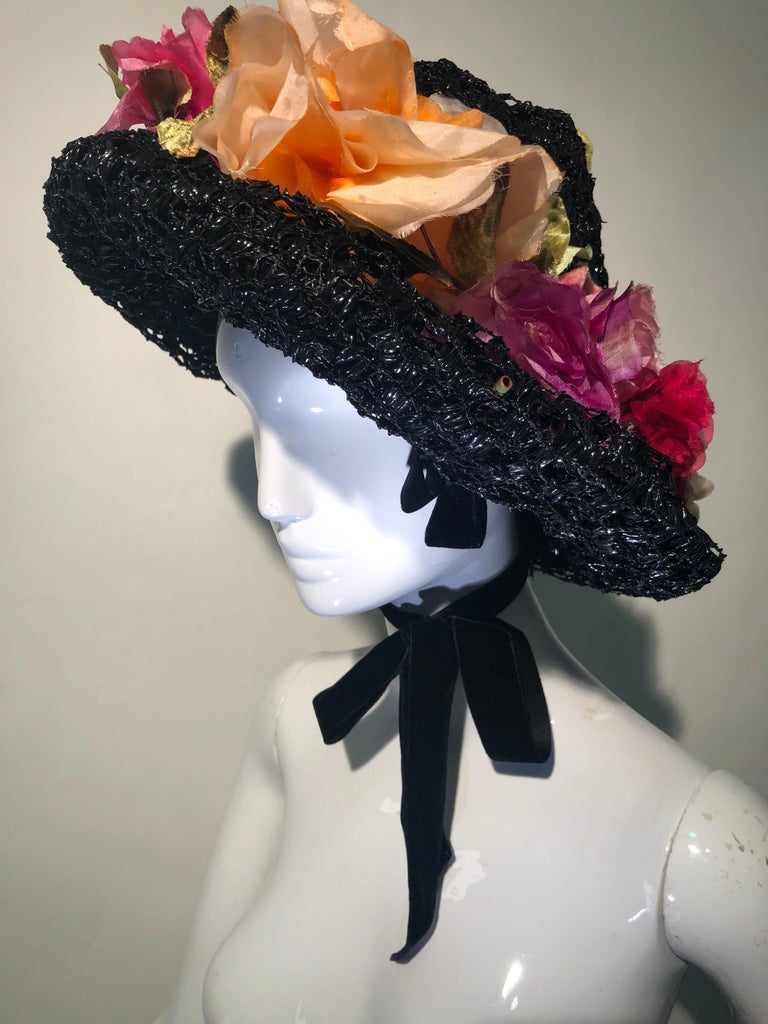 This superb couture 1950s Irina Roublon multi-color, silk floral trimmed hat is a hand-made beauty. Multiple layers of lacquered black veiling make up the body with a soft-peaked crown. So chic! Hat is secured by ribbon tie behind ears.