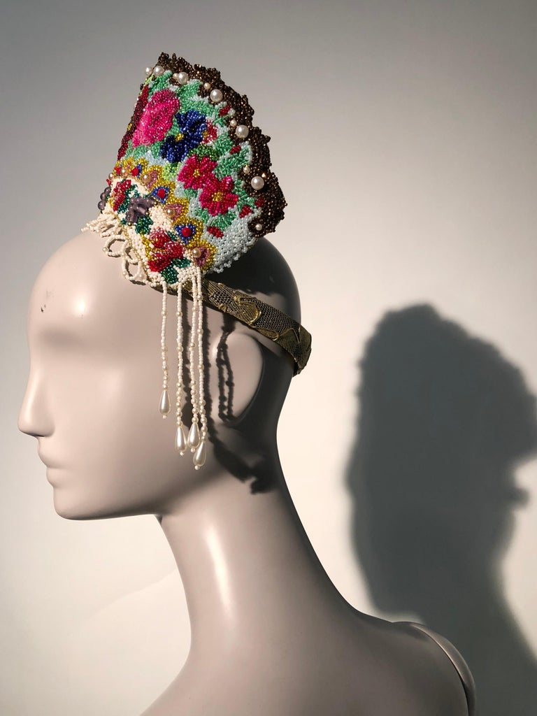 A completely hand-beaded and finished Torso Creations mantia-style crown or headdress. Multicolor beaded florals tower over the top of this stunning accessory which is finished in back with antique gold embroidered lace. Headband trimmed in lace