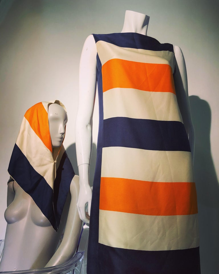 A wonderful 1960s Mod Teal Traina color-blocked orange navy and ivory silk shift dress with matching head scarf! Dress has hook and eye closures at one shoulder and slips on. Sleeveless and lined, this is perfect for a resort get-away!