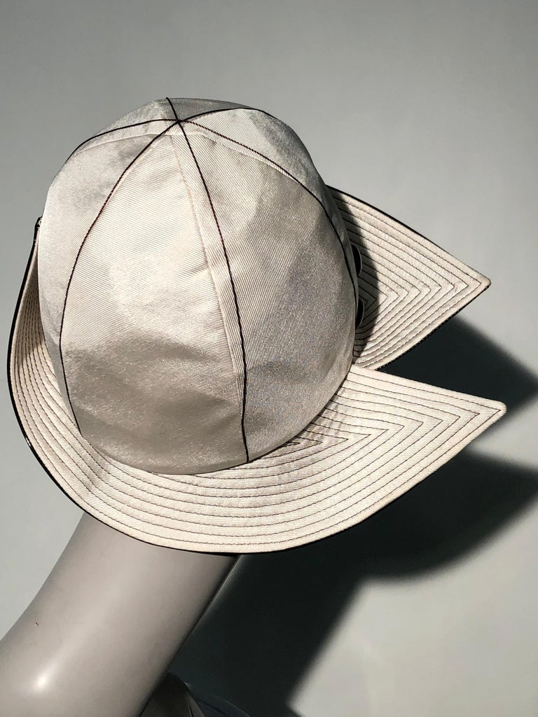 A fabulous 1960s Mr. John ivory faille dome-shaped Mod style hat with wide trapunto-stitched brim in brown patent leather. Brim is split at side. Two brown patent leather buttons adorn the side. A surprisingly cheery floral lining inside.