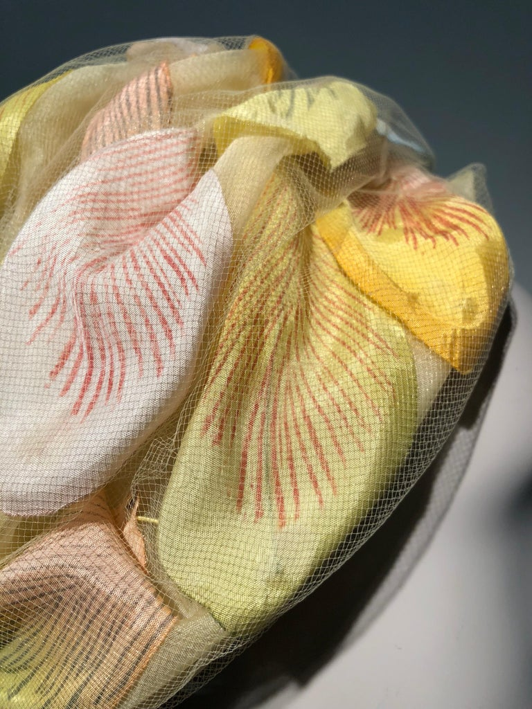 A beautiful 1960s Christian Dior pale yellow silk beehive turban-style hat with large pastel magnolia-like silk petals captured under a layer of silk tulle. Divine. Size Medium.