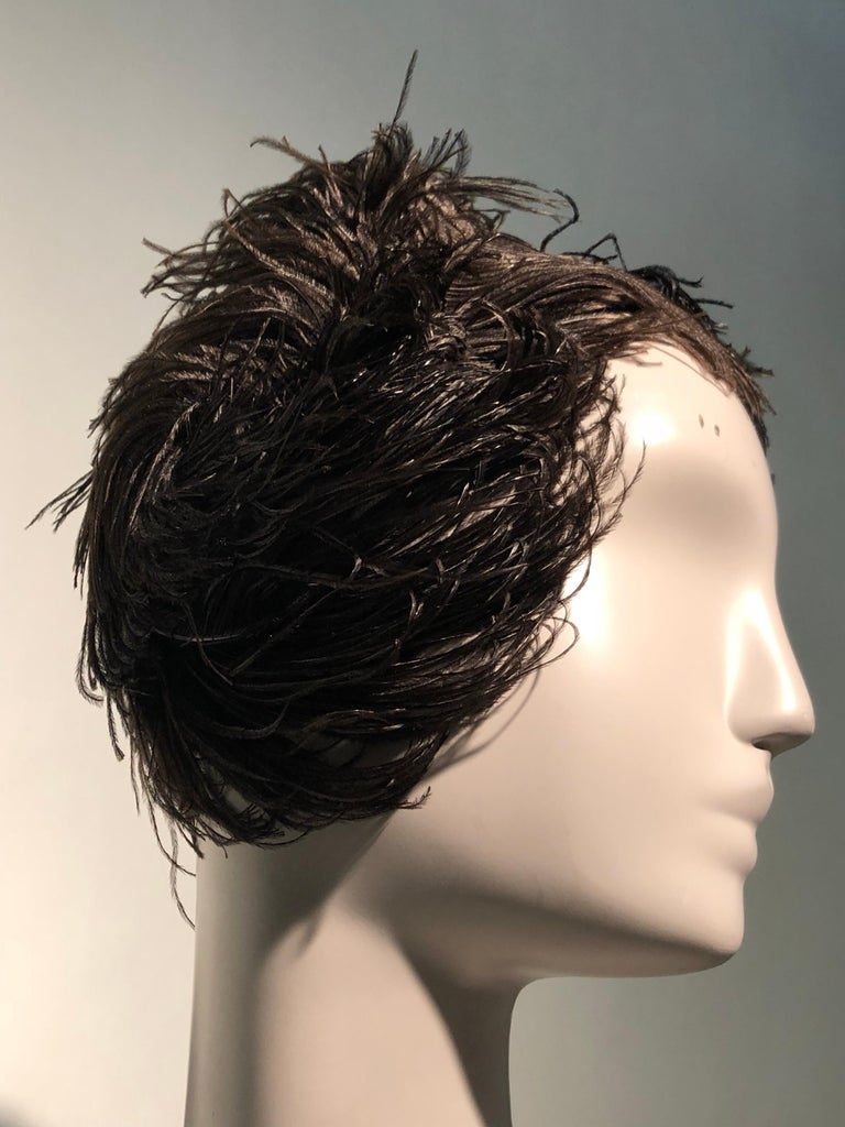 A beautiful 1950s Christian Dior ballet-inspired black ostrich feather cocktail hat that swirls around the head dramatically. Rather wig-like at the back of the head and at neckline. Worn toward crown.