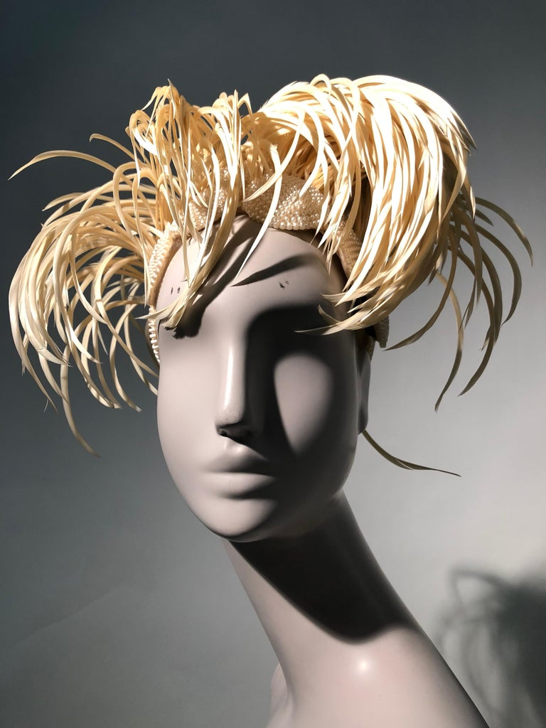 A fabulous and rare 1950s Bes-Ben cream exotic feather and faux pearl medallion hat. Couture-style soft construction with organza lining.  With their signature whimsical style, Bes-Ben creates a knock-out statement.