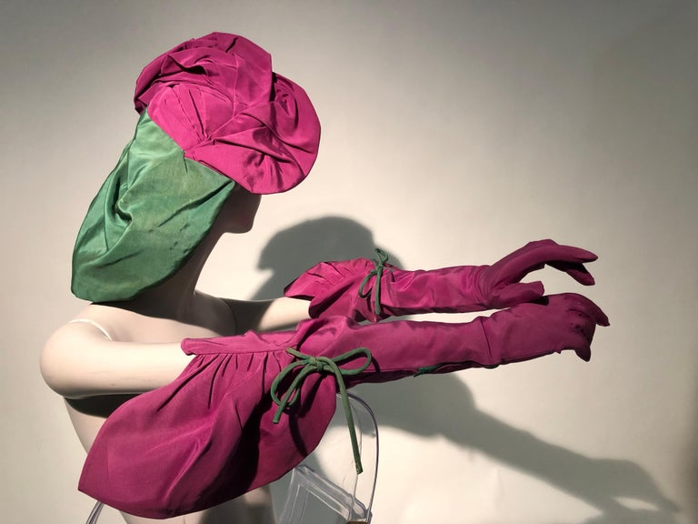 A bold 1940s Sally Victor Hollywood hat and glove ensemble: a tilt-style fuchsia and green snood, in faille attached to a hat with matching faille opera length gloves. Gloves feature an extreme gauntlet gathered with a green cord tie. Has been