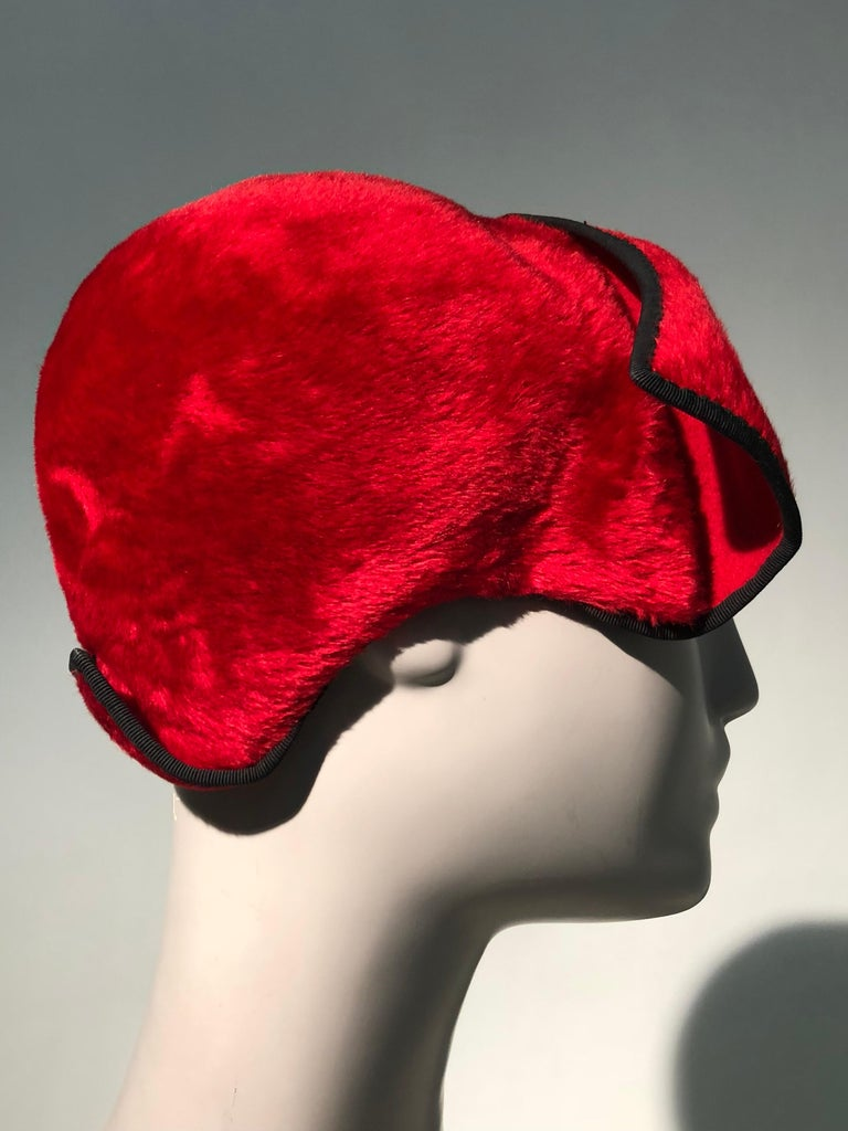 An unusual 1950s John Frederics red fur felt close-fitting cloche cap with black  binding at edges and turned back corners cut into the form at front and back.  Size Small to Medium.