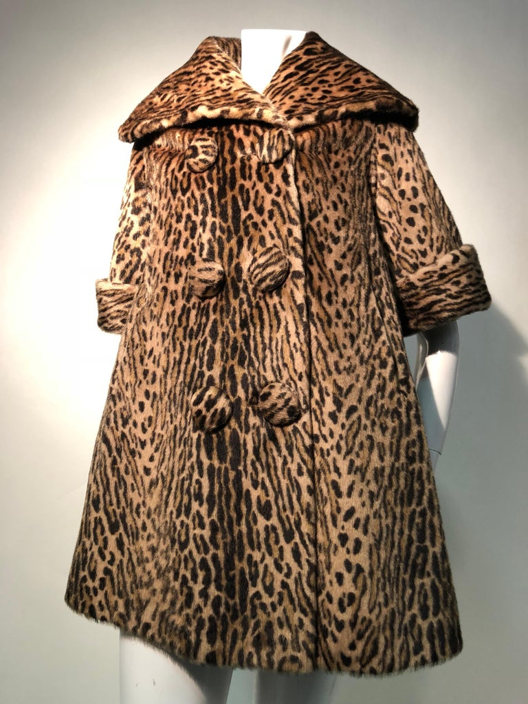 A fantastic 1950s Kashan faux leopard fur double-breasted three quarter length sleeve swing coat with large collar. Can be worn up to ward off a stiff breeze. A great look with longer gloves for winter. Fully lined. This is of the quality of faux