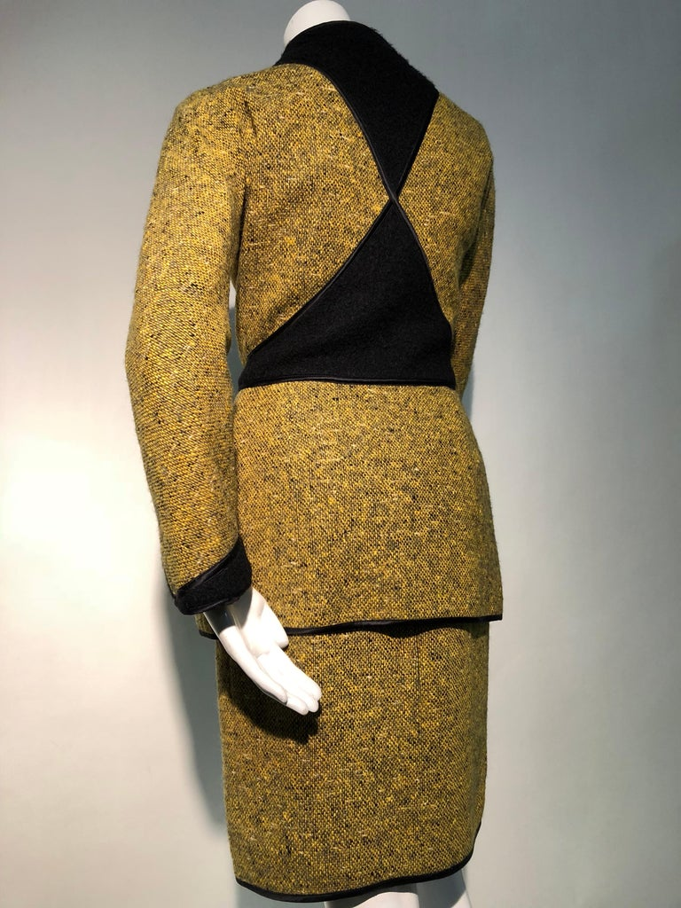 An exquisitely tailored, sleek 1990s Geoffrey Beene 2-piece ensemble in goldenrod and black tweed with geometric pieced panels of black wool and satin piping. The dress is a tweed skirt joined to a black wool blouse giving it the appearance of