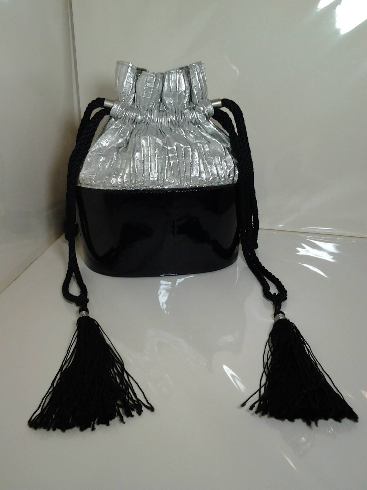 A fabulous 1980s Kansai Yamamoto black patent leather and silver lame bucket bag with silver dragon motif and heavy cord and tassel drawstring.