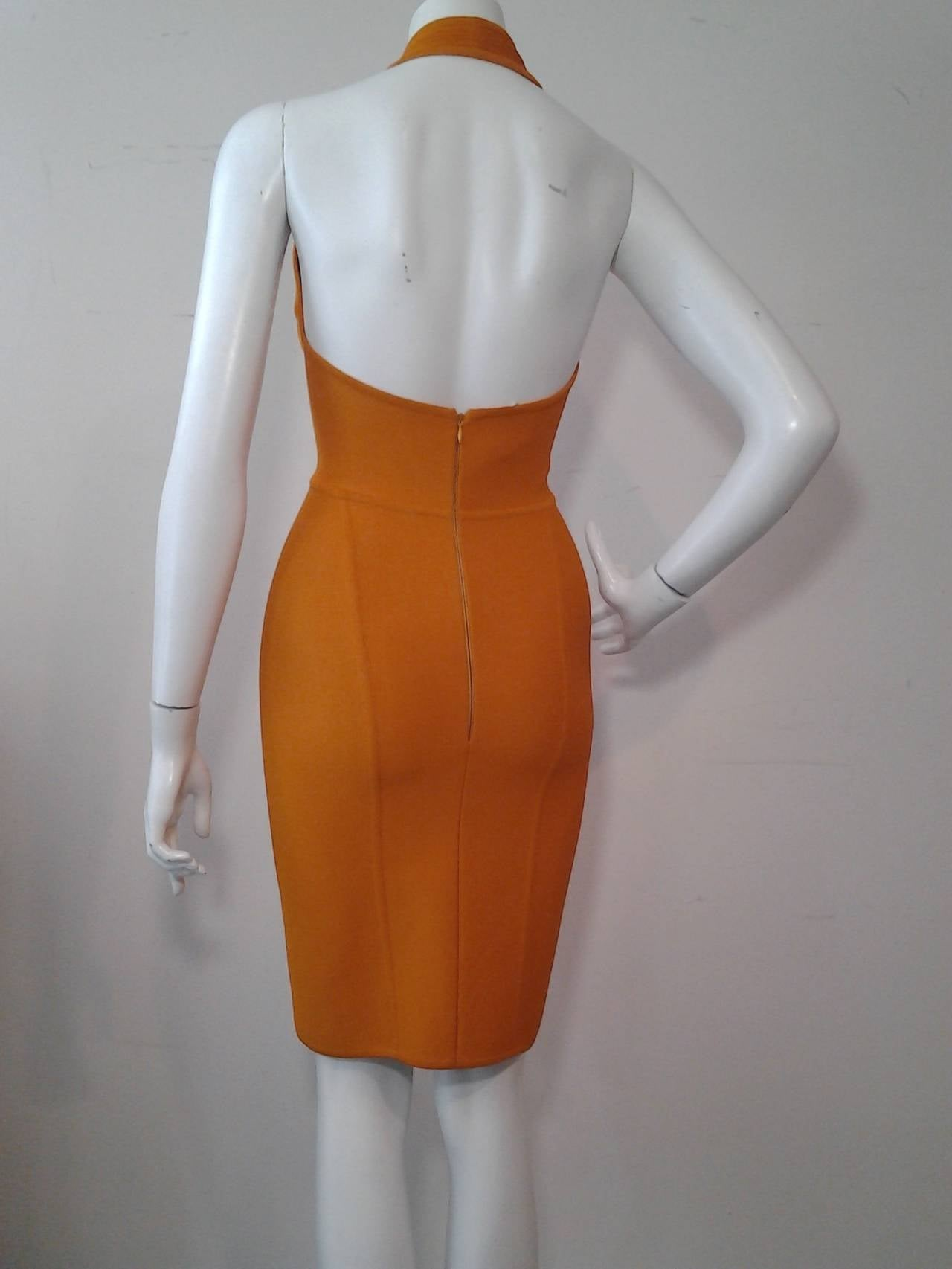 A sexy Herve Leger orange rayon and lycra knit halter dress with zipper back and contour detailing.  Featured on cover of Vogue in 2006.