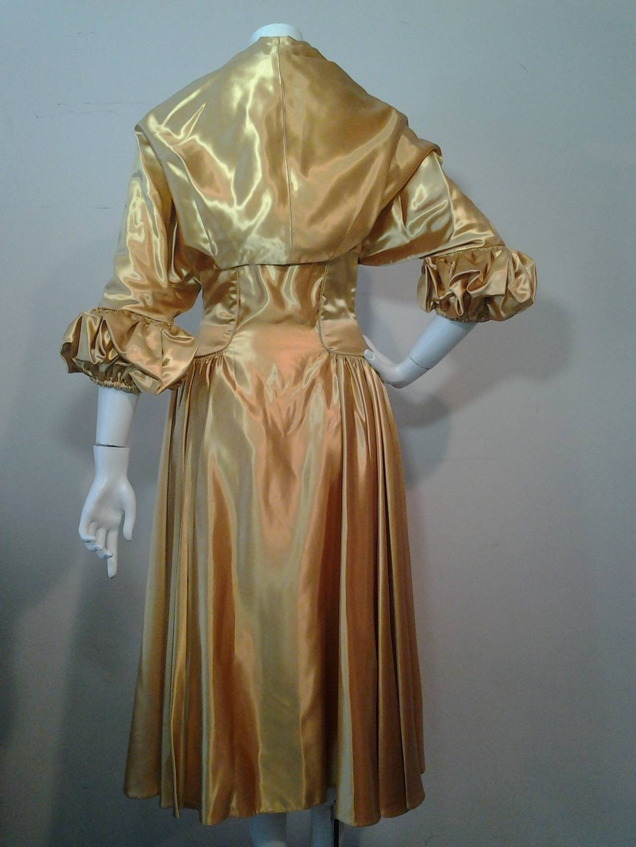 "A gorgeous, unmarked as to maker, 1950s gold silk satin strapless dress and jacket ensemble:  dress features a full skirt and constructed zipper back bodice with unusual ""V"" shaped front detailing reminiscent of a 16th Century stomacher. Jacket is a"