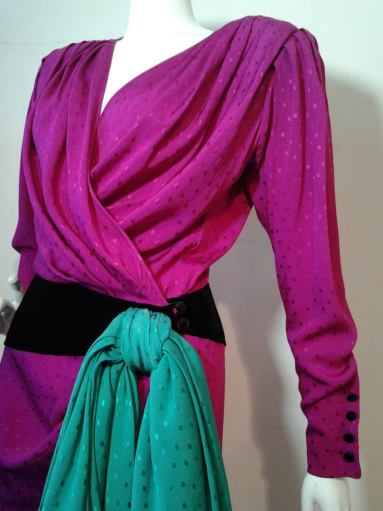 A fabulous 1980s Emanuel Ungaro fuchsia silk wrap evening gown with black velvet contour fitted hip band and dramatic emerald green draped floor length bow at side.  Glass 4-button cuff on sleeves. Slight dolman sleeve and shoulder pads.