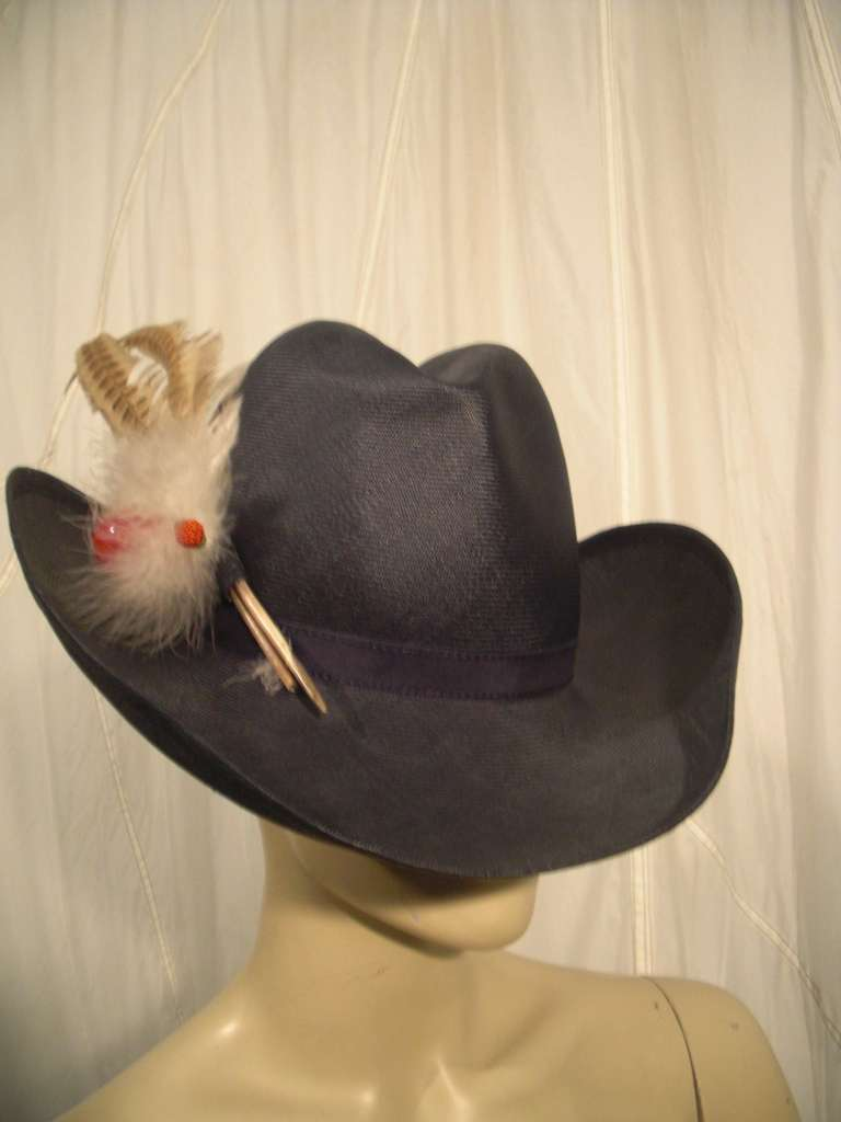 A jaunty 1970s Adolfo II Western style navy blue straw hat with turned up brim and creased crown.  Pheasant feather spray with faux fruit trimming.