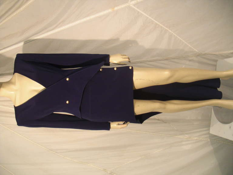 """A 1990s Claude Montana navy silk crepe skirt suit:  Jacket is low plunging with metal double-breasted buttons and side which dips to a point.  Skirt is a wrap around """"cut-away"""" skirt with metal side buttons. Very long in back, very short in front."""