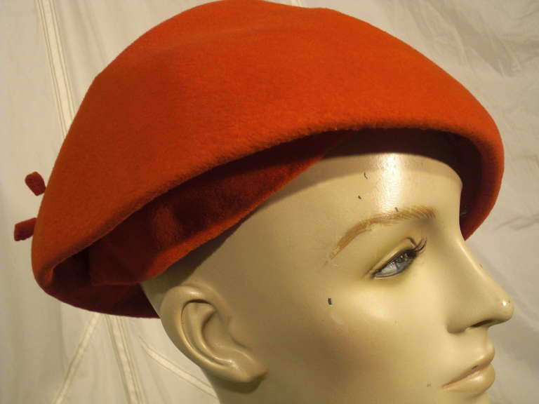 A stylish 1950s hat by Emme: Sueded persimmon colored cashmere fabric covers a bullet shape structured crown. Inside is a fitted soft cap with three combs to secure firmly.  Two matching original covered hat pins.