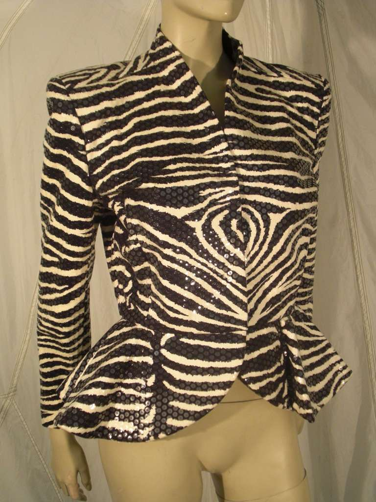 A fantastic 1980s Travilla evening jacket:  sequin glazed zebra print with hook and eye closures, strong shoulder silhouette and flared peplum.  Silk satin lined.