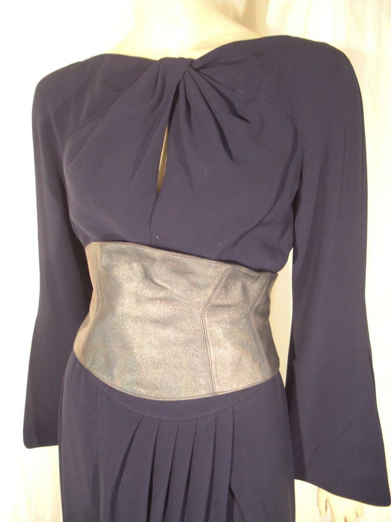 A wonderful 1980s Thierry Mugler Couture navy blue rayon dress with keyhole twisted neckline, faux wrap style pleated front at waist and a separate gunmetal leather snap-on contoured cummerbund. Low draped back. Side zipper.