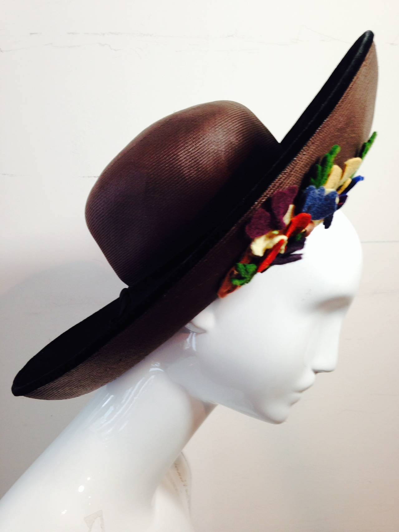 A lovely 1940s Irina Roublon brown, finely woven straw hat:  Large upturned brim is embellished underneath with detailed felt cut-out basket and bouquet details. Top side of brim is covered in black felt. Intended to be worn back on crown of head to