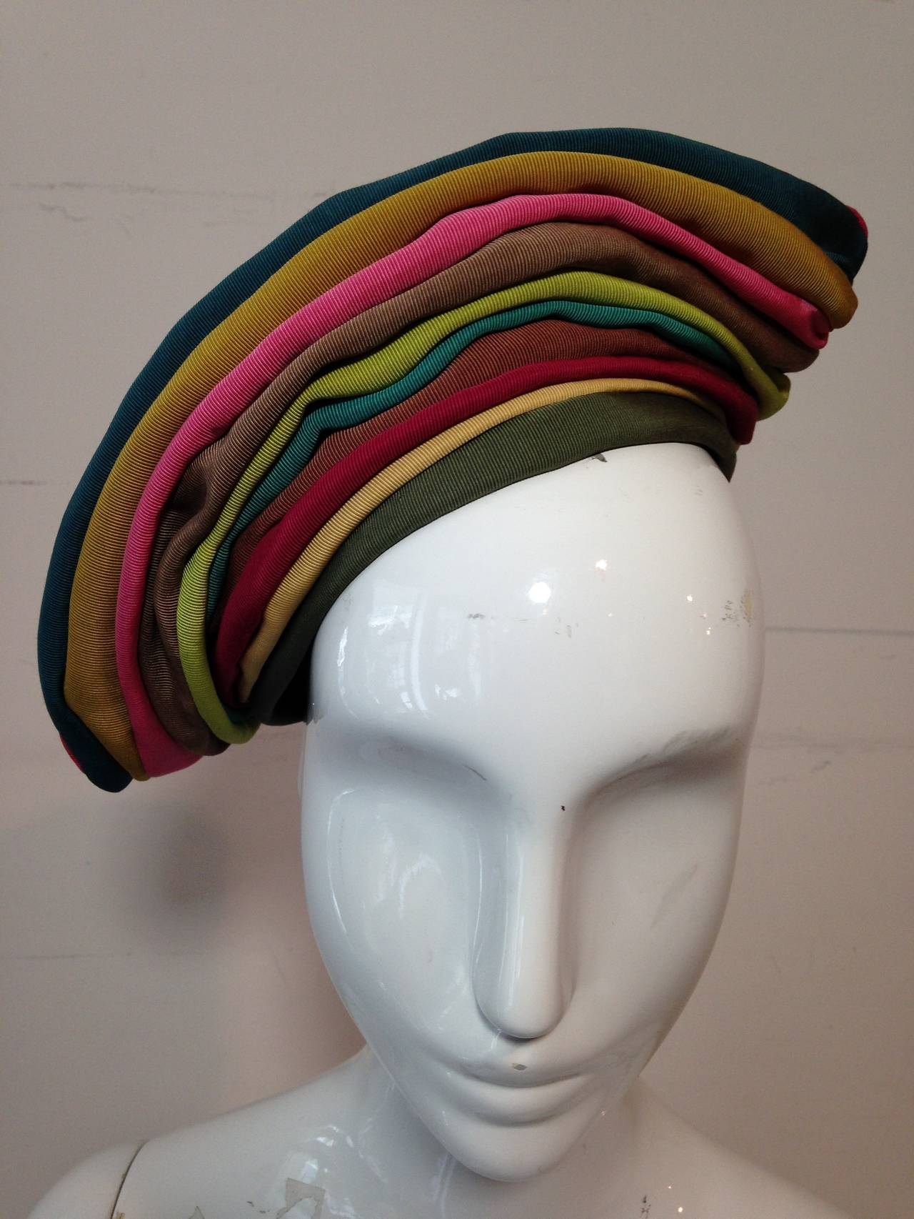 A fabulous 1940s Irina Roublon hat:  Multi-color grosgrain ribbons are stitched together in stripes at a jaunty tilt in this stunning hat lined in silk tulle. This hat is meant to perch on head and not pulled down all around.  Secure with pins or