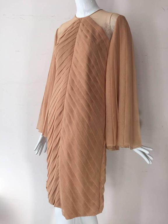 1980s James Galanos peach blush silk chiffon pleated cocktail dress with heavily pleated fan-sleeves.  Hand rolled hem on sleeves. Body constructed with 4 layers of silk chiffon. Completely lined. Original hem.  Back gold-tone buttons.