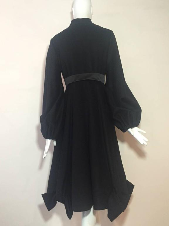 A beautiful Givenchy black wool and cashmere Princess style coat:  Banded neck with hidden snap closures. Silk satin empire waistband. Balloon tucked snap-closure sleeves.  Full skirt with interesting sculpted bow detail at hem.  Rayon floral satin