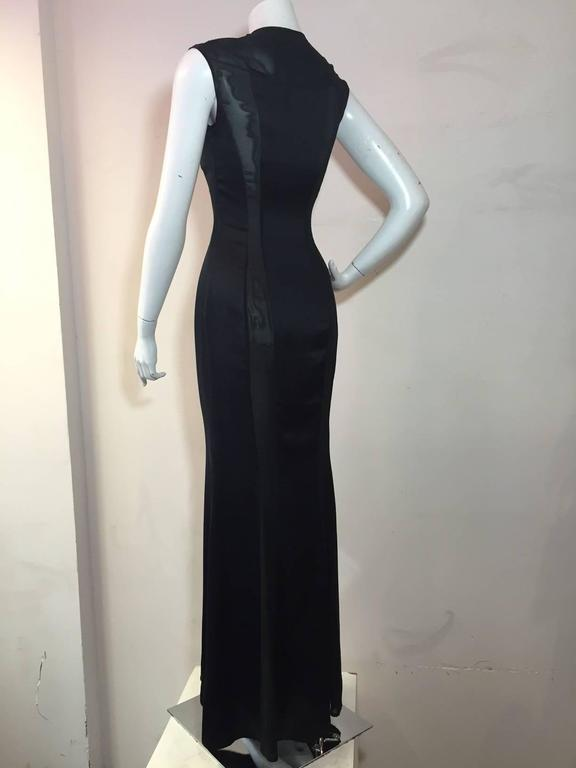 A 1990s  Richard Tyler silk satin gown in black with daring sheer silk and lycra chiffon panels running the length of the gown giving it a body conscious fit.  Flared fishtail hem.  Snap closures at shoulder.